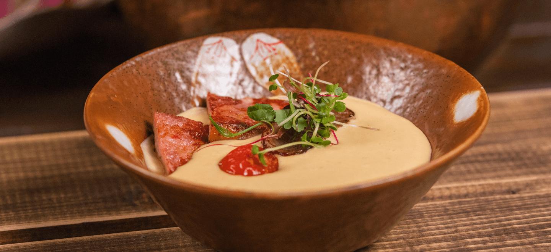 Чечевичный крем-суп с ломтиками ветчины и жареными томатами